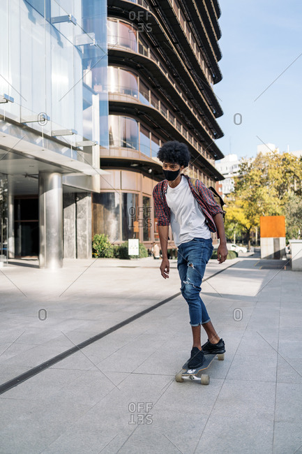 Cool afro boy wearing face mask due to covid19 doing skate in the city with his longboard in Madrid, Spain