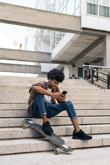 Handsome young african guy sitting in stairs next to his longboard and using his phone in Madrid, Spain