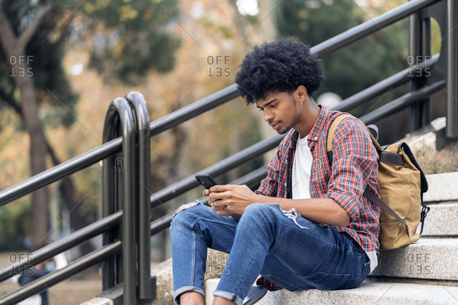 Handsome young african guy sitting in stairs and using his phone in Madrid, Spain