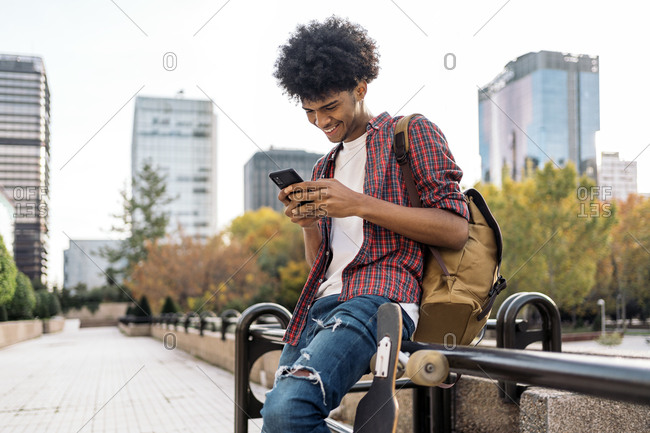 Handsome african boy having fun in the city and using his cellphone in Madrid, Spain