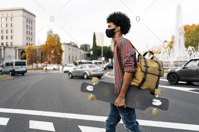 Young afro boy wearing face mask due to covid19 walking in the city in Madrid, Spain
