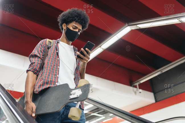 Young african boy wearing face mask due to covid19 using phone and holding a longboard in Madrid, Spain