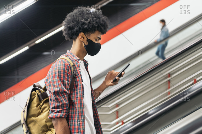 Young african boy wearing face mask due to covid19 using phone in Madrid, Spain