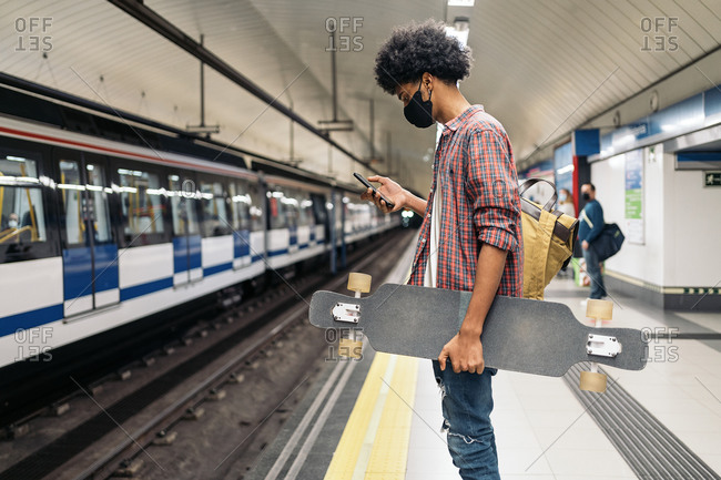 Young boy wearing face mask due to covid19 using his phone while waiting in the underground in Madrid, Spain