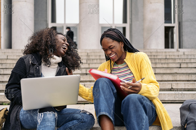 Cheerful black friends using laptop while sitting in stairs and doing homework in Madrid, Spain