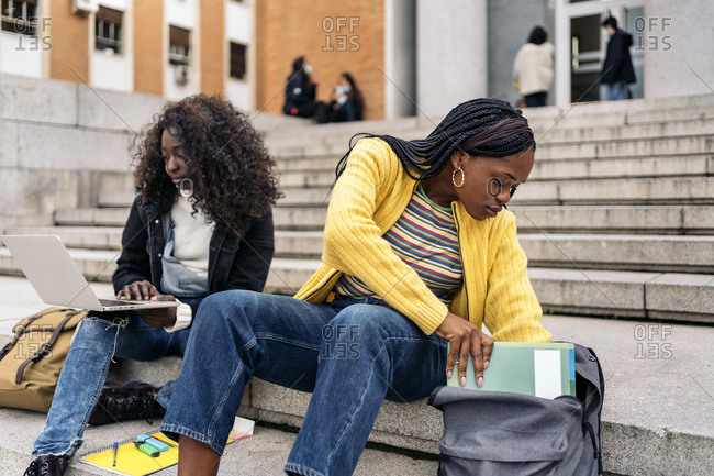 Black friends using laptop while sitting in stairs and doing homework in Madrid, Spain