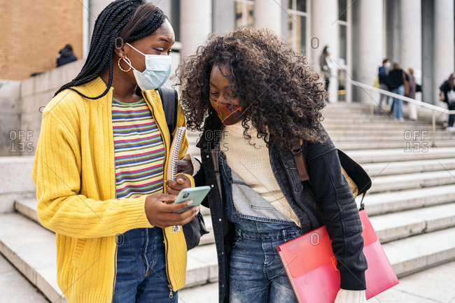 Black female students talking and using phone wearing face mask due to covid19 in Madrid, Spain