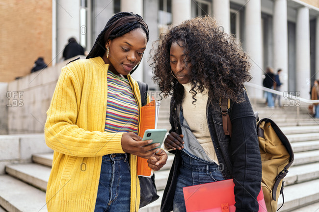 Black female students talking and using phone outside the college campus in Madrid, Spain