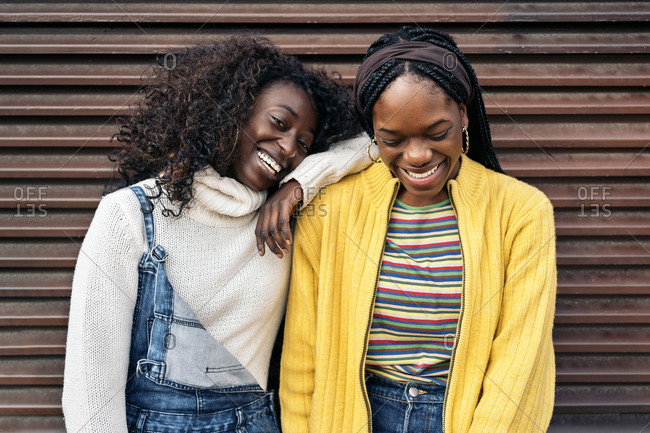 Black young friends smiling and looking at camera