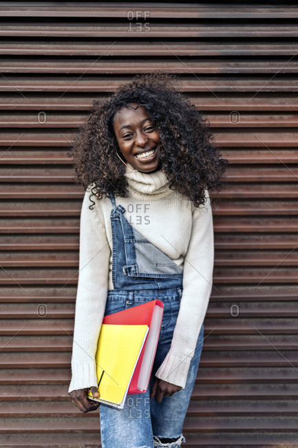 Young black girl holding notebook, smiling and looking at camera in Madrid, Spain