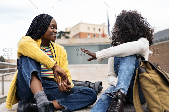 Happy female black friends laughing and enjoying evening in the city in Madrid, Spain