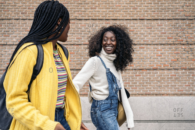 Black young friends smiling and walking in the street in Madrid, Spain