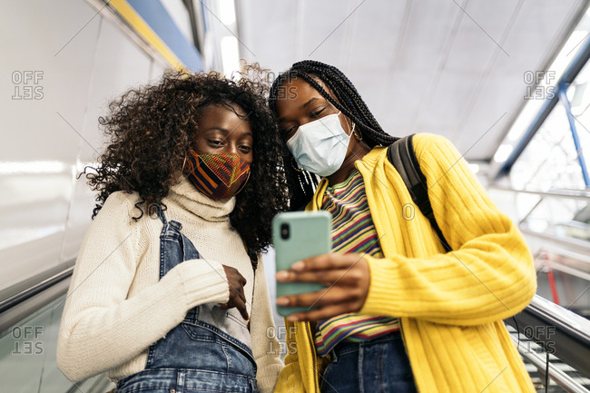 Young black friends wearing face mask due to covid19 looking at phone while using escalators in Madrid, Spain