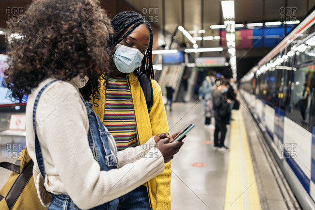 Young black friends wearing face mask due to covid19 looking at phone while waiting in the underground in Madrid, Spain