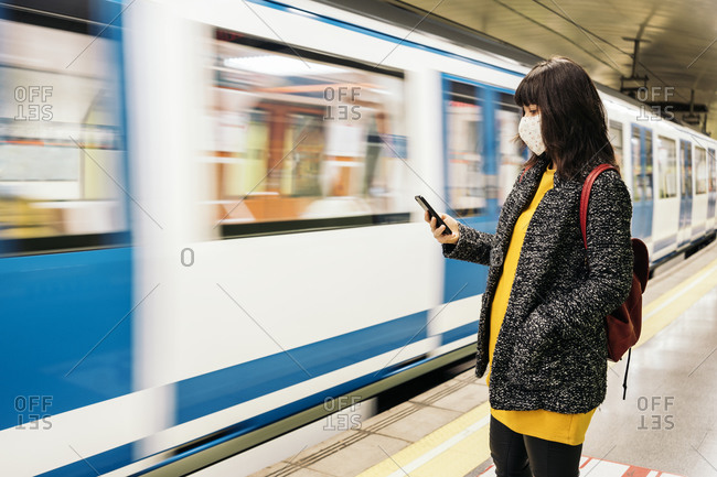Adult woman wearing face mask due to covid19 using her phone while the metro arrives in Madrid, Spain