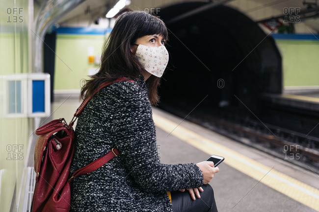 Adult woman wearing face mask due to covid19 sitting in a bench while the metro arrives in Madrid, Spain