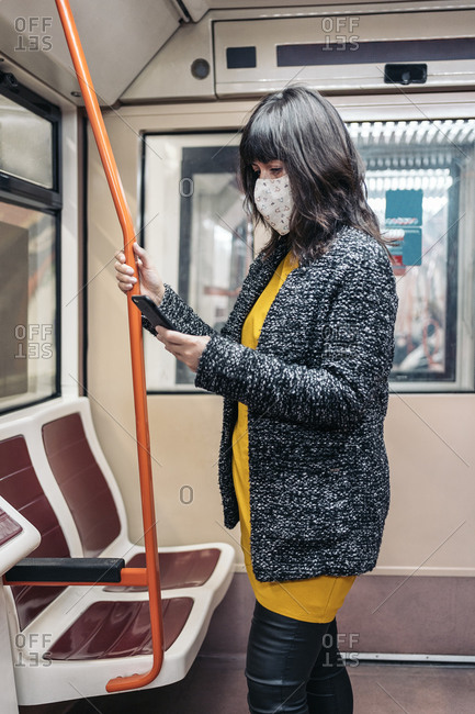 Stylish woman wearing face mask due to covid19 inside metro wagon using her cellphone in Madrid, Spain