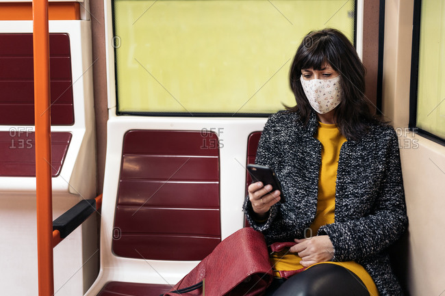 Stylish woman wearing face mask due to covid19 sitting inside metro wagon and using her cellphone in Madrid, Spain