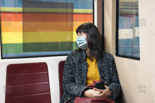 Stylish woman wearing face mask due to covid19 sitting inside metro wagon looking through the window in Madrid, Spain