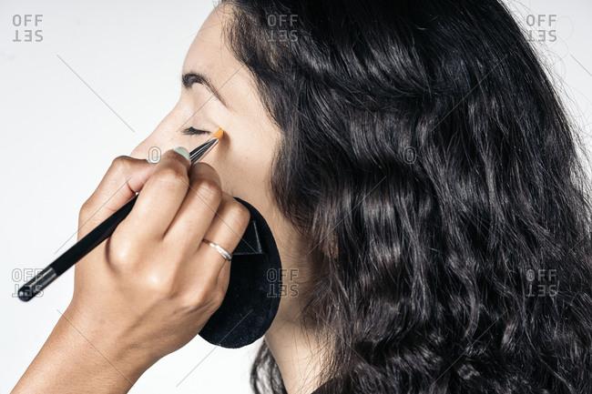 Faceless woman doing eye makeup to caucasian girl in studio in Madrid, Spain