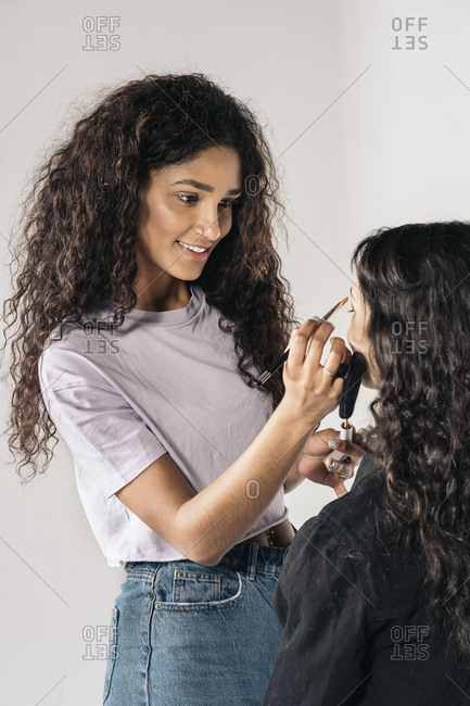 Happy make up artist using brush to apply foundation to client in Madrid, Spain