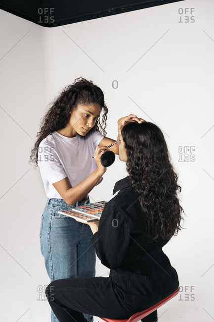 Young latin woman doing make up to her client in studio over white background in Madrid, Spain