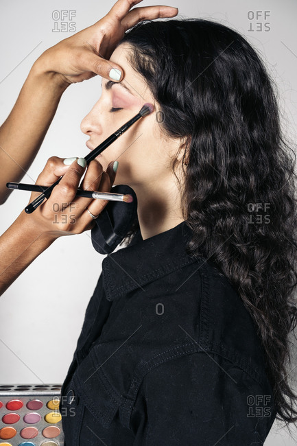 Young make up artist doing makeup to pretty model in studio in Madrid, Spain