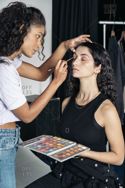 Concentrated make up artist using eye shadow for her client's look in Madrid, Spain