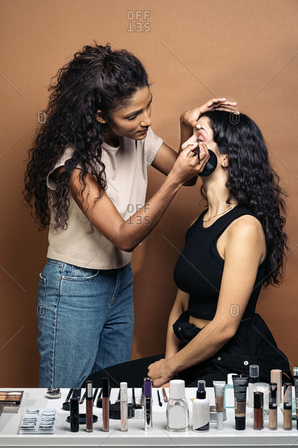 Cool makeup artist doing makeup to her client in studio in Madrid, Spain She is doing her eyeliner in Madrid, Spain