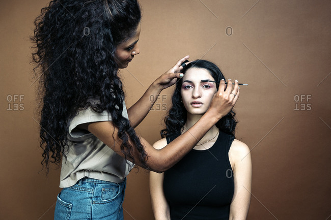 Young model having her makeup done by professional artist in studio in Madrid, Spain
