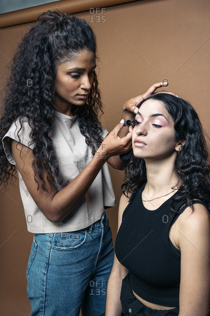 Cool makeup artist doing makeup to her client in studio in Madrid, Spain She is applying eyelash mascara in Madrid, Spain