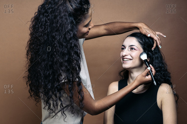 Cool makeup artist doing makeup to her smiley client in studio in Madrid, Spain