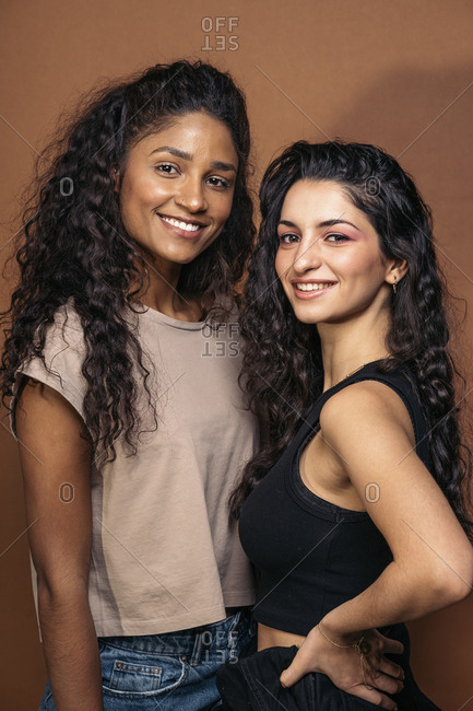 Latin woman and her friend smiling and looking at camera over brown background in Madrid, Spain