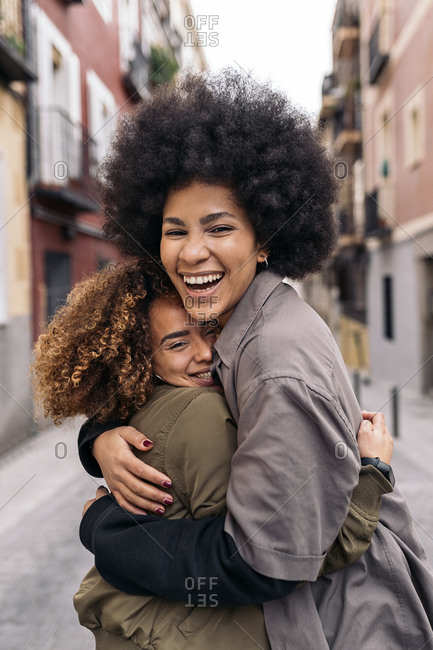 Lovely afro girls hugging in the street and looking at camera in Madrid, Spain