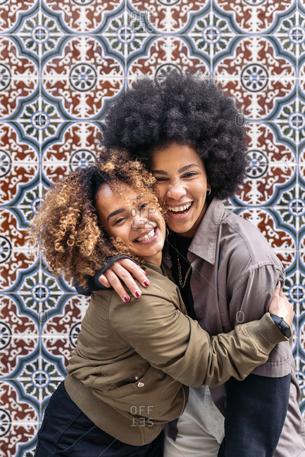 Lovely afro girls hugging each other and looking at camera in Madrid, Spain
