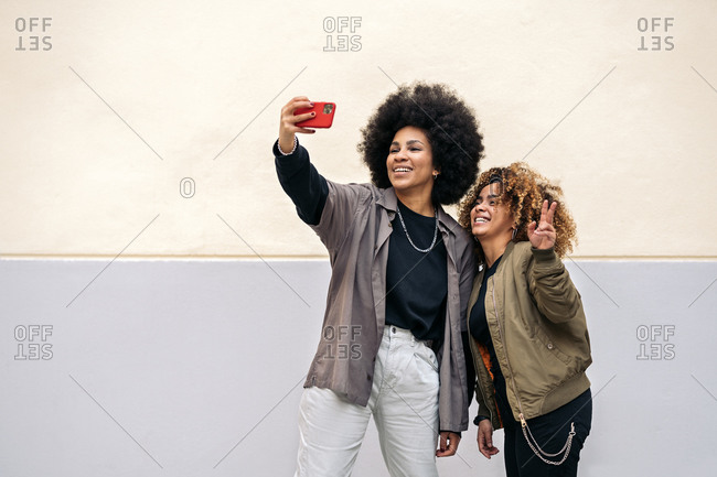 Beautiful african american friends taking picture with phone in Madrid, Spain