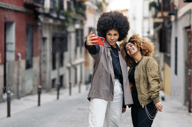 Beautiful african american friends taking picture with phone in the street in Madrid, Spain