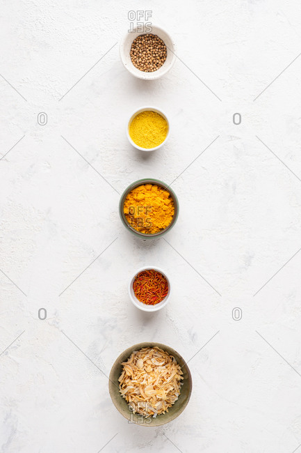 Overhead view of assorted yellow spices and ingredients over white background
