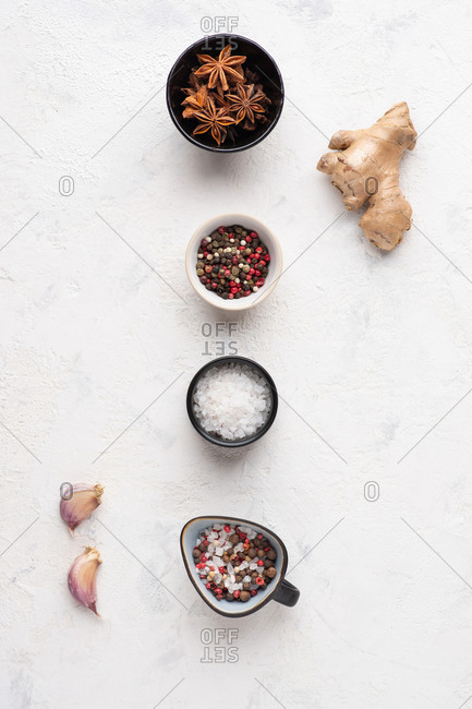 Overhead view of assorted spices and ingredients over white background. Ginger, star anise, salt, pepper, garlic