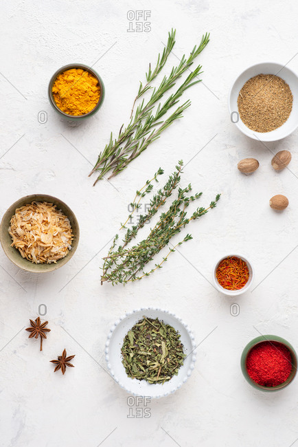 Overhead view of assorted spices and ingredients over white background