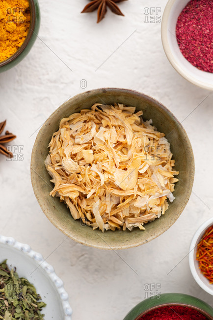 Overhead view of bowl with dried onion amidst assorted spices and ingredients over white background