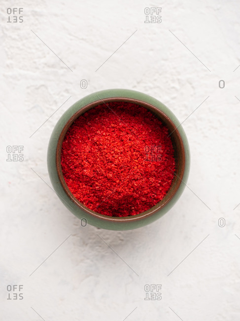 Overhead close-up view of red ground paprika in small bowl over white background