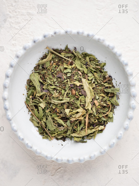 Overhead view of dry mint leaves in bowl over white background