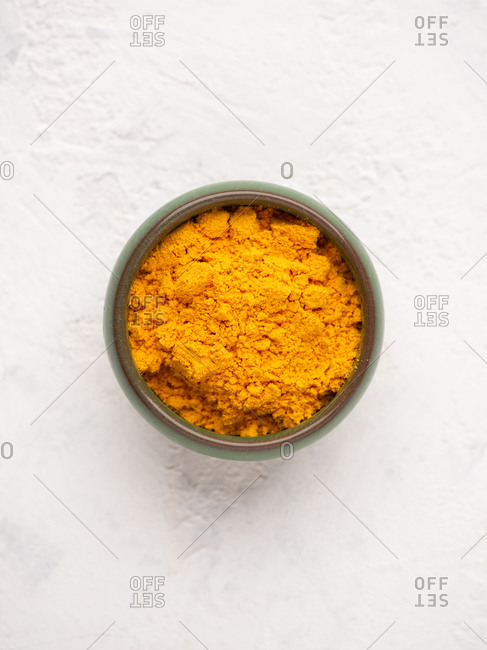 Overhead close-up view of bowl with yellow ground curcuma over white background