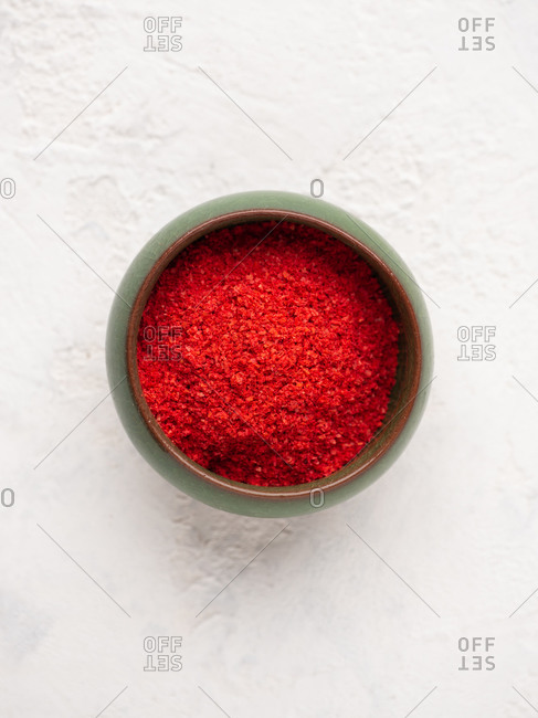 Overhead close-up view of red ground paprika in small green bowl over white background