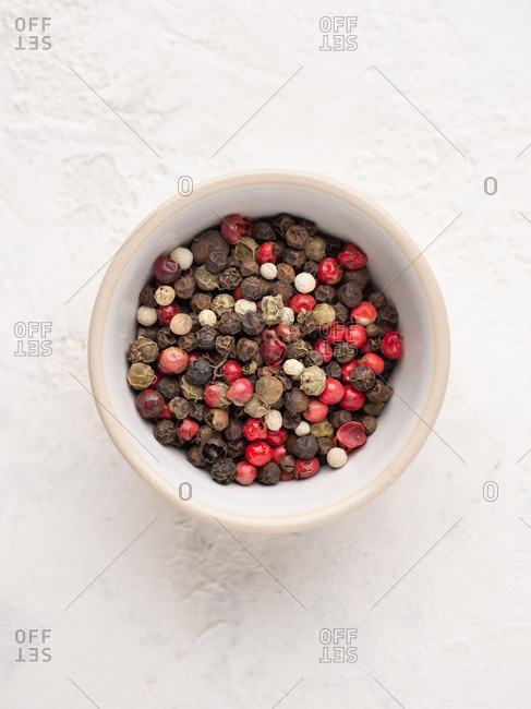 Overhead view of bowl with various sorts of pepper over white background