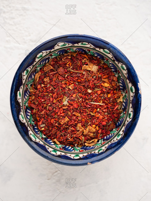 Overhead view of assorted spices in ceramic bowl over white background
