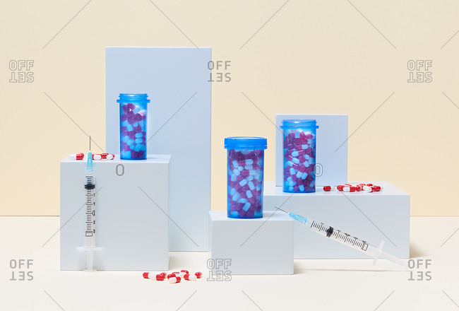 Red and white medicine capsules in bottles and syringes on blocks in the medical concept