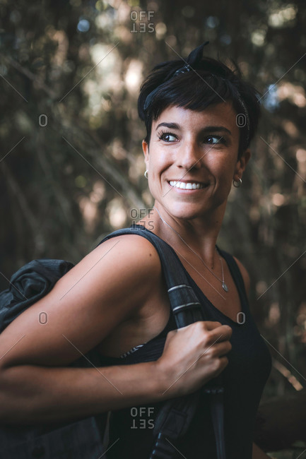 Close up portrait of a beautiful woman with short hair smiling in the forest while hiking and enjoying nature wearing a backpack in the woods looking away holding the strap