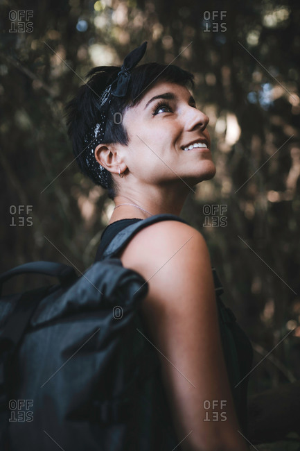 Close up portrait of a beautiful woman with short hair smiling in the forest while hiking and enjoying nature wearing a backpack in the woods looking up